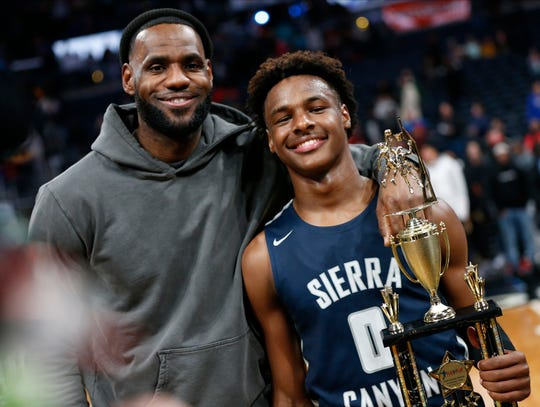 LeBron James, left, poses with his son Bronny after Sierra Canyon beat Akron St. Vincent - St. Mary in a high school basketball game Saturday.