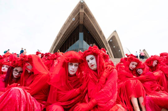 The Red Rebels, part of the Extinction Rebellion Australia demonstrator group, participate in a climate protest rally in Sydney on Dec. 15, 2019. Protesters rallied in front of the landmark Sydney Opera House demanding urgent climate action from Australia's government, as bushfire smoke choking the city caused health problems to spike.