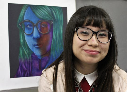 """Cooper High School senior Summer Revell, posed by an earlier self portrait titled simply """"Me."""" """"I'm not good at titles,"""" she said. Her mixed media work of the Abilene Philharmonic Orchestra using gouache, watercolor and colored pencil graces the Christmas Day print edition of the Abilene Reporter-News."""