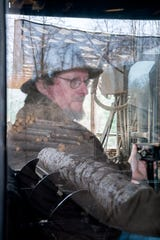 """Don Shuford runs the controls on a saw as logs are reflected in the glass at Sunrise Sawmill on Nov. 26, 2019. """"I've been doing this forever,"""" Shuford said with a laugh. """"They'll probably just take me and bury me in the sawdust pile when we're done."""""""