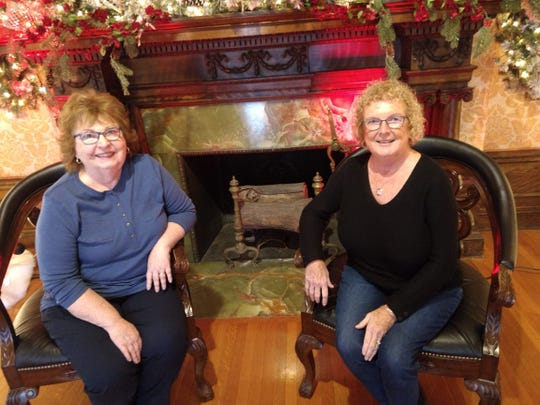 Jackie Ferguson, left; and Rosanne Brunner sit by the fireplace inside the Roberson Mansion. Both are volunteers for the Roberson Museum and Science Center.