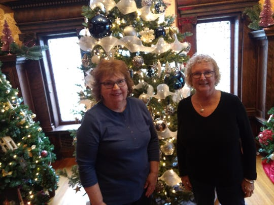 Rosanne Brunner, left, and Jackie Ferguson admire a Christmas tree inside the Roberson Mansion. Both are volunteers for the Roberson Museum and Science Center.