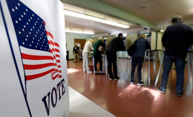 In this Nov. 6, 2018, file photo, voters cast their ballots, in Gates Mills, Ohio. An Associated Press review has found that thousands of Ohio voters were held up or stymied in their efforts to get absentee ballots by mail in 2018's general election because of a missing or mismatched signature on their ballot application.