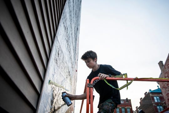 """Owen """"Tenzing"""" Gunderman assists with """"Cin City"""" mural by Lindz and Lamb at Blink Cincinnati in Over-the-Rhine on Thursday, October 10, 2019."""