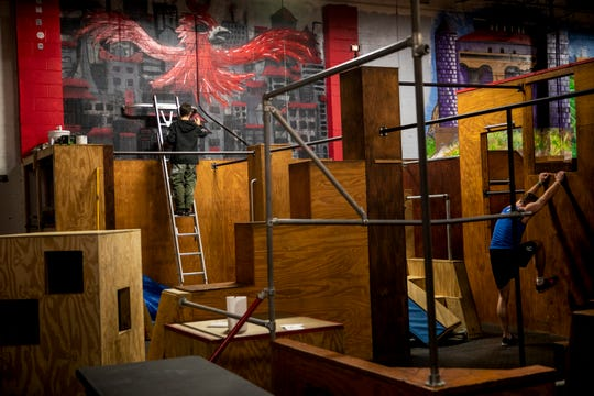 """Owen """"Tenzing"""" Gunderman paints a mural on a wall inside Swift Movement Studio, a Parkour gym in Winton Place on Friday, November 15, 2019."""