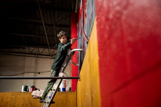 """Owen """"Tenzing"""" Gunderman, 17,  paints a mural on a wall inside Swift Movement Studio, a Parkour gym off Mitchell Avenue in Winton Place on Friday, November 15, 2019.  Tenzing is a senior at Clark Montessori. He is also a professional artist, award-winning muralist and the youngest participant in Blink's Secret Walls competition –which, he won."""