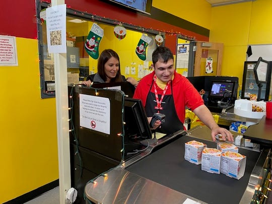 Teacher Jessica DiMino works with a student on a register in the on-campus ShopRite.