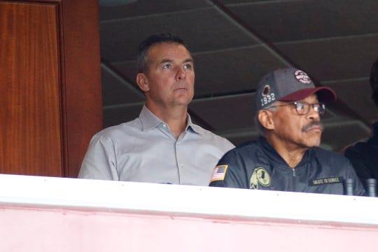 Three-time national champion college football coach Urban Meyer, center, watches Sunday's Philadelphia-Washington game.