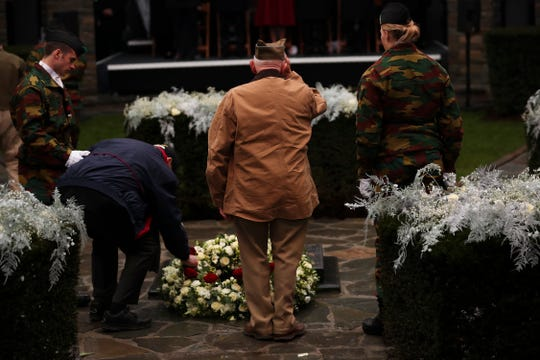 U.S. Battle of the Bulge veterans put flowers to pay tribute during a ceremony to commemorate the 75th anniversary of the Battle of the Bulge at the Mardasson Memorial in Bastogne, Belgium, on Monday, Dec. 16, 2019.