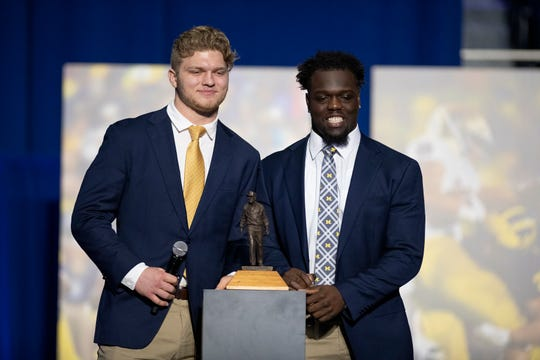 Michigan's Aidan Hutchinson, left, and Kwity Paye, pose with a Shemmy after being named the team's Defensive Linemen of the Year on Sunday.