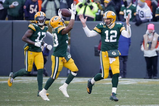 Packers' Aaron Jones celebrates his touchdown run with quarterback Aaron Rodgers during the second half on Sunday.