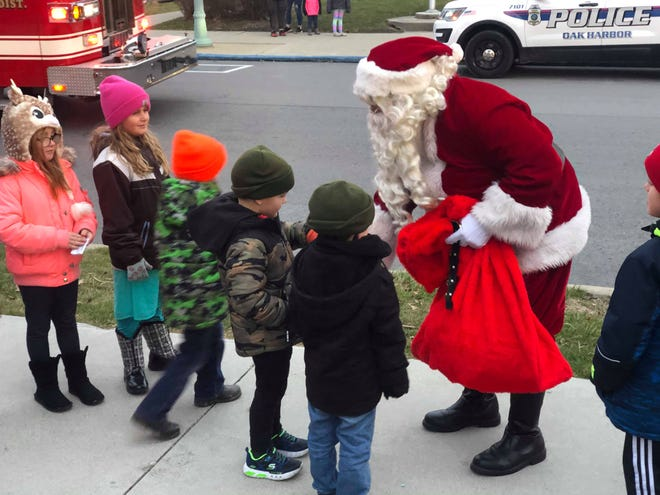 Santa Claus arrived in Oak Harbor on a Portage Fire District truck on Dec. 7 and greeted children.