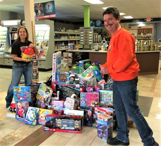 Bikers Memorial Fund members Joanne Darr and Glenn Bliss donate toys to the Sandusky County Toys for Tots on Dec. 6.