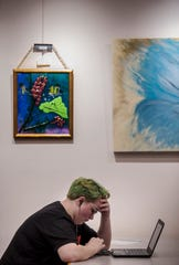 Cape Coral resident Emily McPhee studies at the Cape Library. The library is currently hosting an art exhibit by the Southwest Florida Fine Craft Guild.