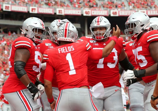 Ohio State quarterback Justin Fields (1) celebrates a 2019 touchdown with offensive lineman Wyatt Davis (52) and Jonah Jackson (73) and Thayer Munford (75).