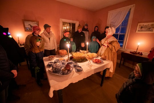 """Guests gather around a tableful of party fare as Mrs. Campbell brags to them about the elegant treats that await her guests. Cakes, exotic fruits and deserts with hidden prizes await the townfolk. Snowfall added to the seasonal spirit at Conner Prairie's """"A Merry Prairie Holiday"""" event, Sunday, Dec. 15, 2019."""