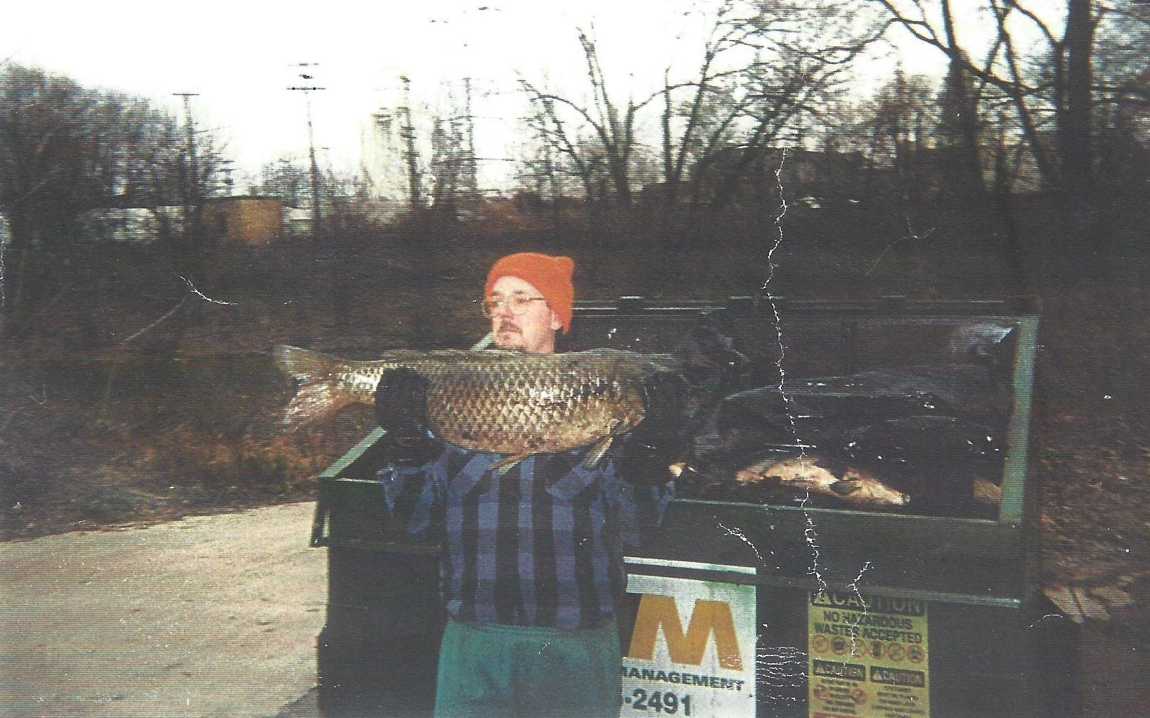 A man carries dead fish from the White River to a dumpster after the Guide spill in December of 1999. The Guide Corp. in Anderson dumped toxic chemicals into the White River, ultimately killing more than 4 million fish through Downtown Indianapolis.