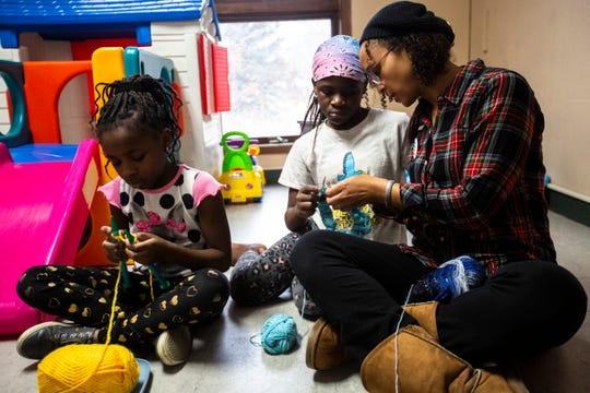 Angie Jordan helps Marie, 11, and her sister Eliza, 9, during a Banjo Knits knitting circle Dec. 14 at the Broadway Neighborhood Center in Iowa City. The sisters have been knitting for four years.