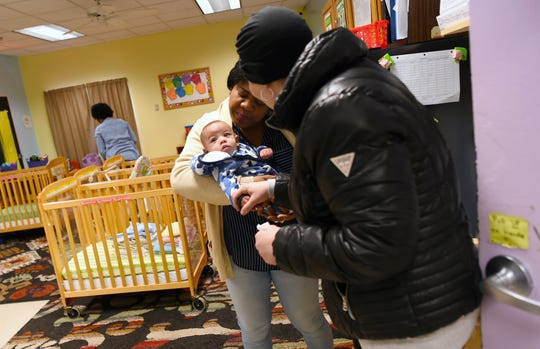 Emily Dilger of Ithaca, right, says goodby to her infant son Phoenix at daycare. Dilger was pregnant with Phoenix when she was diagnosed with with non-Hodgkin lymphoma.
