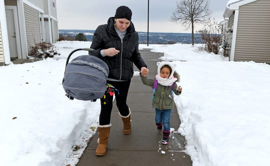 Emily Dilger of Ithaca carries her baby son Phoenix and holds her daughter Penelope's hand as they leave their Ithaca apartment for daycare. Dilger is a single mother who was diagnosed with non-Hodgkin lymphoma while she was pregnant.