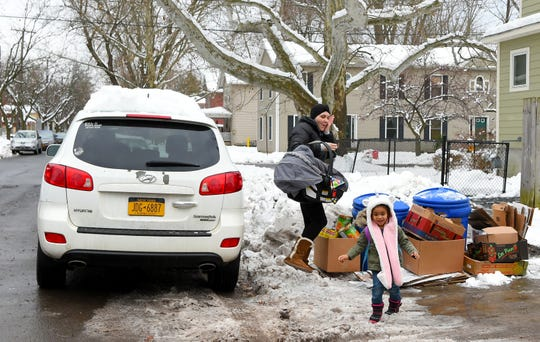 Emily Dilger of Ithaca reacts to being hit by a snowball thrown by her three year old daughter Penelope as she drops Penelope and her infant son Phoenix at daycare. Dilger, a single mother of three, was diagnosed with non-Hodgkin lymphoma while she was pregnant.