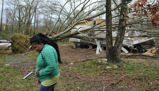 Atalaya Price, of Edwards, walks by what's left of her new mobile home after a tornado ripped through her neighborhood around noon, Monday, Dec. 16, 2019. Price and her four children, none of whom were at home when the storm hit, moved in just two weeks ago.