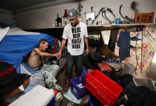 Brent Spradlin, left, fist bumps Jeff Gill, founder of Hip Hop Cares street outreach, as he took a break from packing his belongings in a homeless camp beneath the I-65 overpass at Brook and Breckinridge streets.  The city has posted signs that they will be removing the camps starting July 12.July 10, 2019