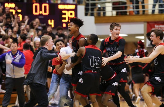 New Albany's Derrick Stevenson (11) screamed as he was swarmed by his teammates after he hit a last second three-point shot to win their game over Floyd Central 39-36 during the sectional tournament at Seymour High School. March 1, 2019