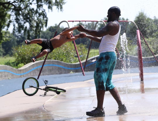 Jyquel Jemison gave his son Josiah Jemison, 2, a swing through the water at the Shawnee Park Sprayground.  His family decided to escape the rising temperatures by cooling down at the park.July 18, 2019