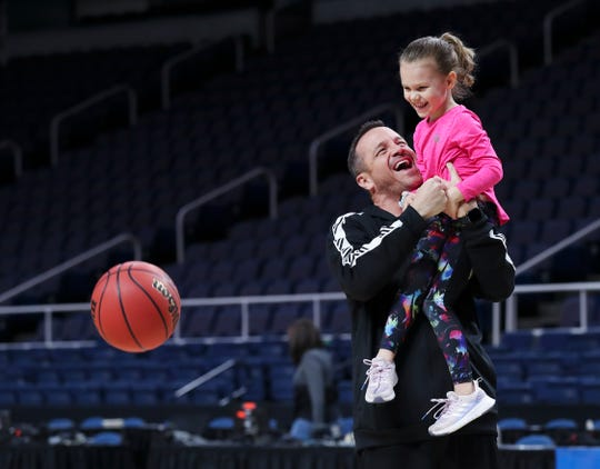 University of Louisville head coach Jeff Walz lifts his daughter Lola, 5, in the air as they shoot hoops with siblings ahead of the team's matchup with UConn in the Elite 8 in Albany, New York.  U of L defeated UConn during their regular season meeting. March 30, 2019