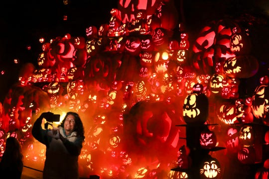 Janet Goldstein took a selfie in front of a pumpkin display at the Jack O' Lantern Spectacular in Iroquois Park in Louisville, Kentucky. Oct. 8, 2019