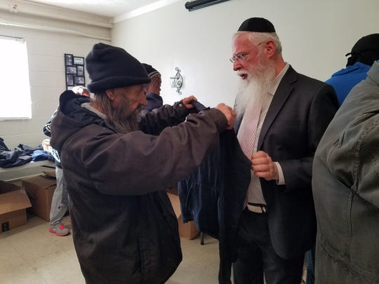 Rabbi Avrohom Litvin helps a man try on a new jacket at a Project Friendship closet in Lexington.