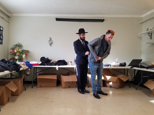 Chaim Litvin helps a man try on a coat at one of Project Friendship's recent outreach.