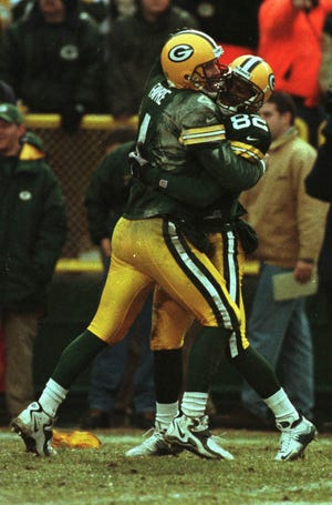 Brett Favre hugs Charles Jordan after Jordan caught a 43-yard pass that took the packers down to the 1-yard line and set up Green Bay's final touchdown of the game in the 1999 season finale.