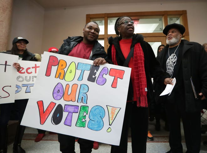 Anita Johnson, left, with Souls to the Polls Milwaukee, demonstrates with Robert Haskins of Milwaukee during a rally at City Hall in Milwaukee on Dec. 16. They were encouraging people to take someone they know to the polls so they can vote in upcoming elections.