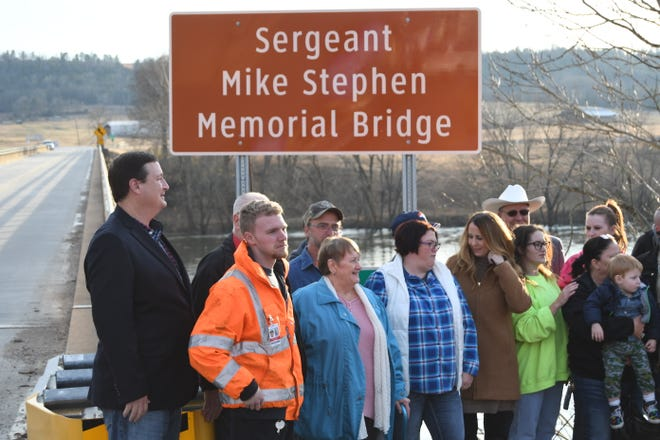 Members of the Stephen family are surrounded by well wishers Friday after a ceremony to dedicate the bridge over the White River in downtown Calico Rock to the memory of Mike Stephen, a Stone County deputy who was killed in the line of duty while responding to a domestic disturbance call.