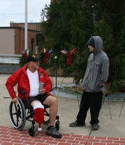 Veteran and Bull Shoals resident Richard Elliott (left) talks to one of the young volunteers helping lay wreaths Saturday as part of the Wreaths Across America event.