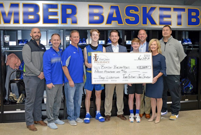 Todd Gilbert and Jodi Strother, accompanied by three of their sons, present a check to Bomber Basketball for the renovation of the boys' locker room. Pictured are (from left) Mountain Home superintendent Dr. Jake Long, assistant coach Brad Morris, athletic director Mitch Huskey, Wyatt Gilbert, Buck Gilbert, Rhett Gilbert, Todd Gilbert, Jodi Strother and head coach Josh Fulcher.