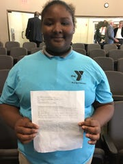 Makiyah Johnson, 13, holds up the paper she read to the County Commission about the YMCA Rising Achievers program and why it's important to her.