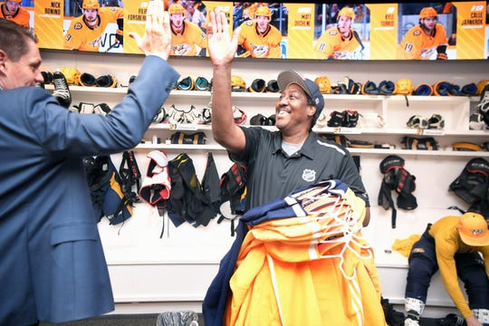Predators clubhouse assistant Craig Baugh high-fives Brandon Walker, Predators Manager of Hockey Operations,  in the team locker room at Bridgestone Arena on Tuesday, Dec. 10, 2019.  Baugh has been with the Predators as a clubhouse assistant since they began the franchise.