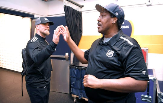 Former Predators hockey goalie and TV analyst for the Nashville Predators Chris Mason high-fives Craig Baugh in the team hallway at Bridgestone Arena on Tuesday, Dec. 10, 2019.  Craig Baugh has been with the Predators as a clubhouse assistant since they began the franchise