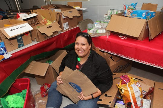 Tamara Lenard was busy passing out bags of donated food items at Saturday's Christmas Giving event.