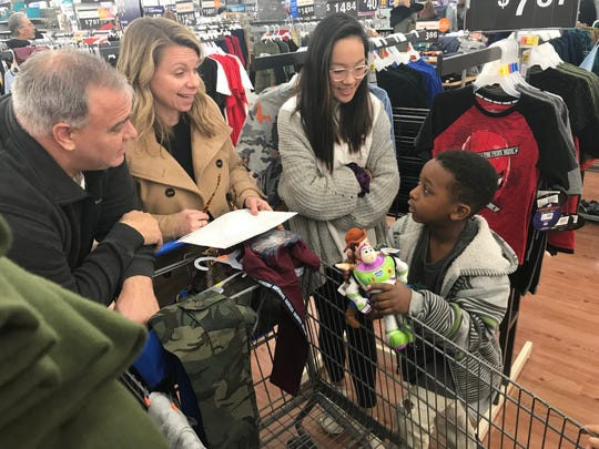 Patrick, Cindy and Miyah Konyn gather took Josiah Calhoun, 5, Christmas shopping for his family. He describes what his two brothers, sister, mother and grandmother will like for Christmas.