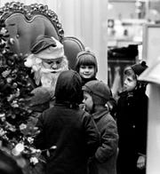 Seven-year-old Cynthia Anderson, center, daughter of Mrs. Lacie Anderson of Berry Street, sits on the lap of Santa Claus as other kids wait their turn at a downtown Nashville department store on Dec. 7, 1968.