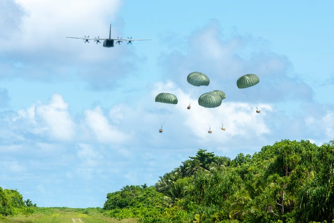 A U.S. Air Force C-130J Super Hercules out of Yokota Air Base, Japan, delivers five Low-Cost, Low-Altitude humanitarian aid bundles filled with critical supplies as part of Operation Christmas Drop 2019 to the island of Woleai, Federated States of Micronesia, Dec. 10, 2019. In its 68th year, OCD is the world's longest running airdrop training mission, providing critical supplies to 55 remote Micronesian islands like Woleai, impacting approximately 20,000 people across 1.8 million square nautical miles of operating area.