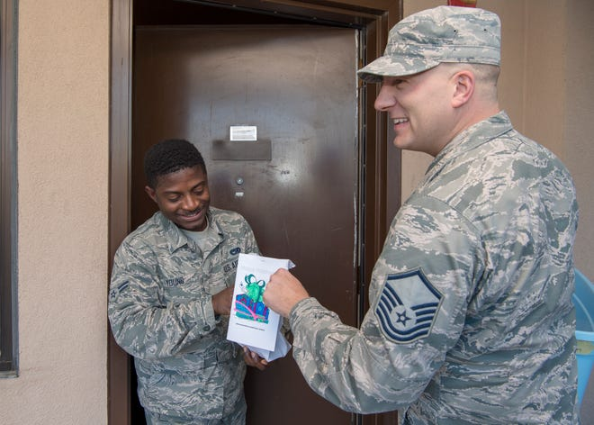 Airman 1st Class David Young, 49th Wing dorm resident, accepts cookies from Master Sgt. Andrew Rother, Cookie Drive volunteer, Dec. 9, 2019, on Holloman Air Force Base, N.M. There were approximately 1200 Airmen on base who received cookies during the annual Cookie Drive.
