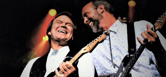 The late Glen Campbell (left) onstage with longtime bandleader Jeff Dayton.