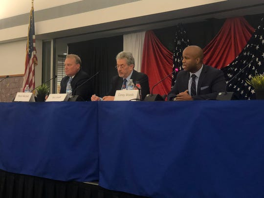 Mark Mithell, left, moderator Vic Linoff and former Councilman Corey Woods during a mayoral forum on Dec. 13, 2019.
