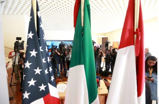 Las bandera de EEUU, México y Canadá se observan en una rueda de prensa relacionada al T-MEC.