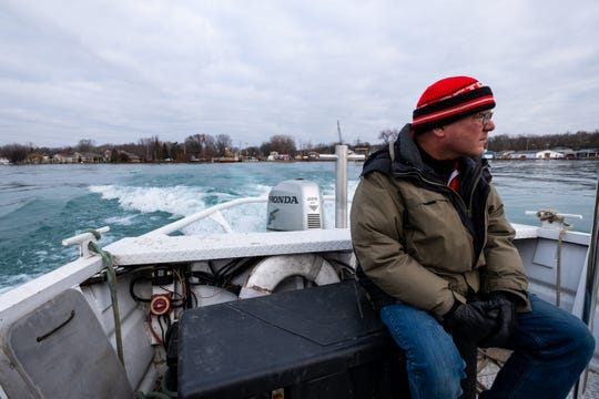 "Tom Dzieciolowski rides on the back of a passenger ferry to Harsens Island Monday, Dec. 16, 2019, in Clay Township. ""We're getting by,"" he said. ""Luckily (my wife's) car got stuck on this side."""